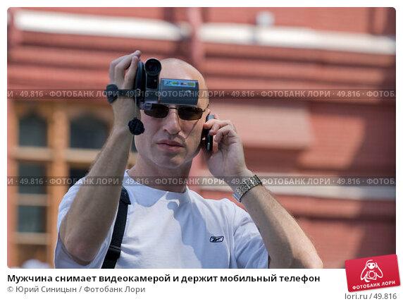 Мужчина снимает видеокамерой и держит мобильный телефон, фото № 49816, снято 30 мая 2007 г. (c) Юрий Синицын / Фотобанк Лори