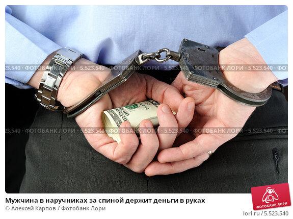 Купить «Мужчина в наручниках за спиной держит деньги в руках», фото № 5523540, снято 21 января 2014 г. (c) Алексей Карпов / Фотобанк Лори