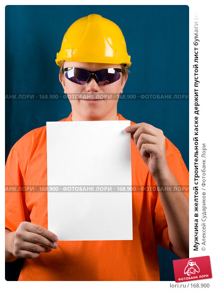 Мужчина в желтой строительной каске держит пустой лист бумаги (clipping path) синий фон, фото № 168900, снято 7 января 2008 г. (c) Алексей Судариков / Фотобанк Лори