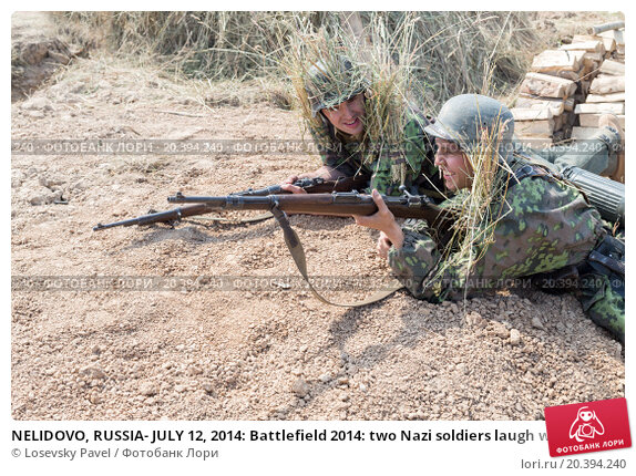 Купить «NELIDOVO, RUSSIA- JULY 12, 2014: Battlefield 2014: two Nazi soldiers laugh with rifles in trench», фото № 20394240, снято 12 июля 2014 г. (c) Losevsky Pavel / Фотобанк Лори