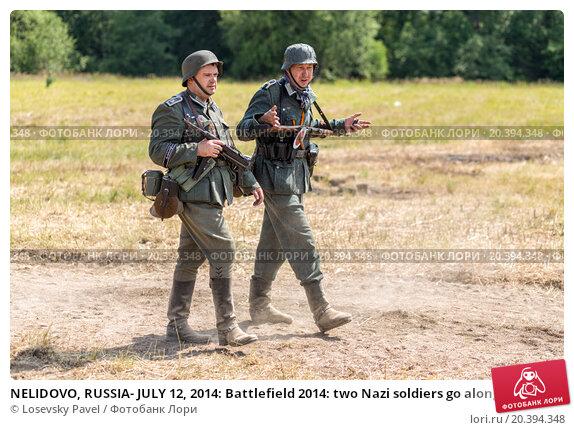 Купить «NELIDOVO, RUSSIA- JULY 12, 2014: Battlefield 2014: two Nazi soldiers go along the dusty road», фото № 20394348, снято 12 июля 2014 г. (c) Losevsky Pavel / Фотобанк Лори