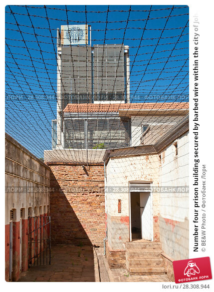 Купить «Number four prison building secured by barbed wire within the city of Johannesburg. South Africa.», фото № 28308944, снято 17 февраля 2019 г. (c) BE&W Photo / Фотобанк Лори
