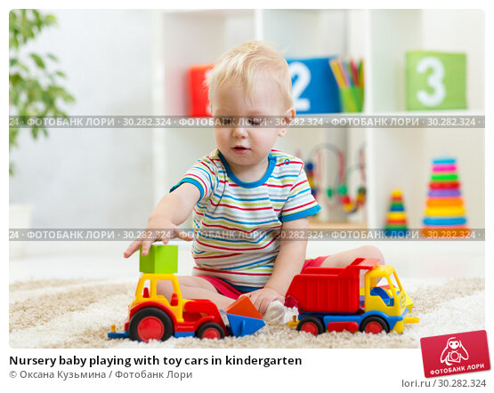 Купить «Nursery baby playing with toy cars in kindergarten», фото № 30282324, снято 15 апреля 2019 г. (c) Оксана Кузьмина / Фотобанк Лори