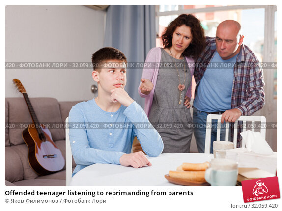 Offended teenager listening to reprimanding from parents. Стоковое фото, фотограф Яков Филимонов / Фотобанк Лори