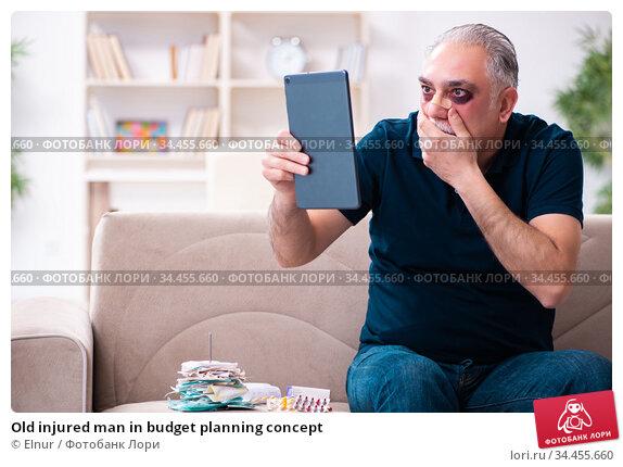 Old injured man in budget planning concept. Стоковое фото, фотограф Elnur / Фотобанк Лори