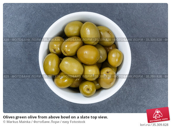 Olives green olive from above bowl on a slate top view. Стоковое фото, фотограф Markus Mainka / easy Fotostock / Фотобанк Лори