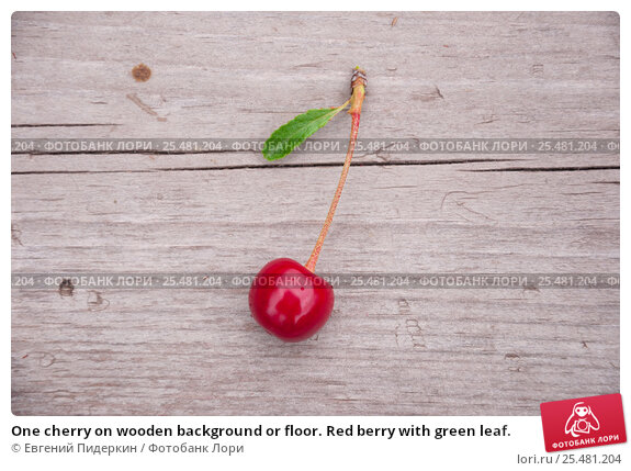 One cherry on wooden background or floor. Red berry with green leaf. Стоковое фото, фотограф Евгений Пидеркин / Фотобанк Лори
