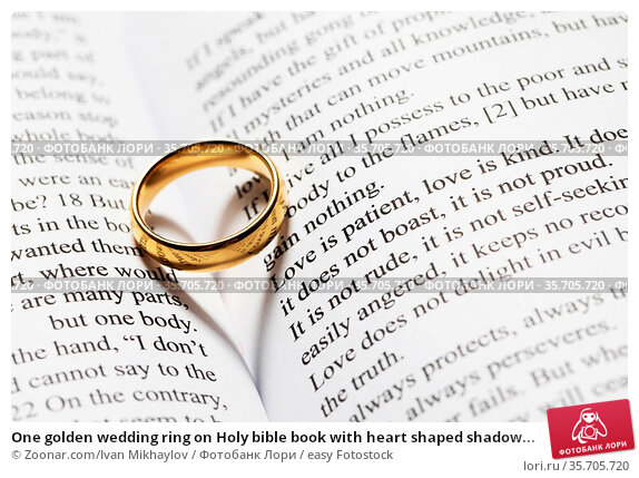 One golden wedding ring on Holy bible book with heart shaped shadow... Стоковое фото, фотограф Zoonar.com/Ivan Mikhaylov / easy Fotostock / Фотобанк Лори
