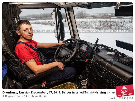 Купить «Orenburg, Russia - December, 17, 2019: Driver in a red T-shirt driving a truck. Inside view of the cab», фото № 34126436, снято 17 декабря 2019 г. (c) Вадим Орлов / Фотобанк Лори