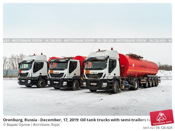 Купить «Orenburg, Russia - December, 17, 2019: Oil tank trucks with semi-trailers tankers parked in the winter», фото № 34126424, снято 17 декабря 2019 г. (c) Вадим Орлов / Фотобанк Лори