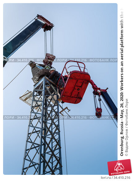 Orenburg, Russia - May, 26, 2020: Workers on an aerial platform with the help of a crane carry out the installation of a wind turbine. Редакционное фото, фотограф Вадим Орлов / Фотобанк Лори