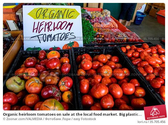 Organic heirloom tomatoes on sale at the local food market. Big plastic... Стоковое фото, фотограф Zoonar.com/VALMEDIA / easy Fotostock / Фотобанк Лори