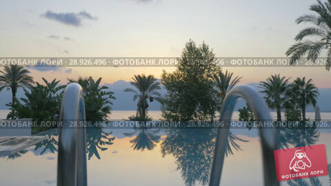 Купить «Outdoor swimming pool on resort. Scene with nature background at sunset», видеоролик № 28926496, снято 1 марта 2018 г. (c) Данил Руденко / Фотобанк Лори