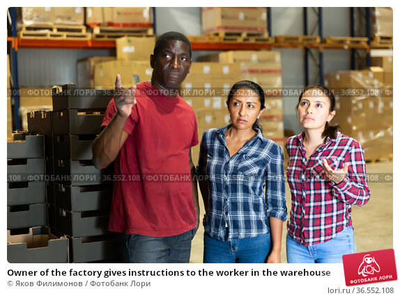 Owner of the factory gives instructions to the worker in the warehouse. Стоковое фото, фотограф Яков Филимонов / Фотобанк Лори