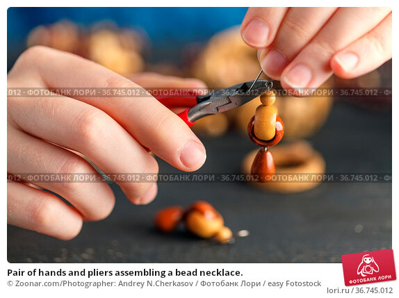 Pair of hands and pliers assembling a bead necklace. Стоковое фото, фотограф Zoonar.com/Photographer: Andrey N.Cherkasov / easy Fotostock / Фотобанк Лори