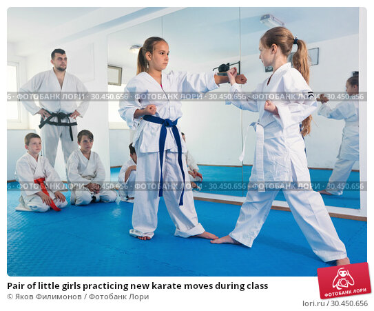Pair of little girls practicing new karate moves during class. Стоковое фото, фотограф Яков Филимонов / Фотобанк Лори