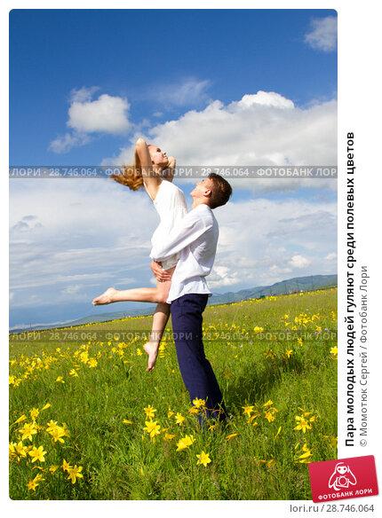Купить «Пара молодых людей гуляют среди полевых цветов», фото № 28746064, снято 25 июня 2018 г. (c) Момотюк Сергей / Фотобанк Лори