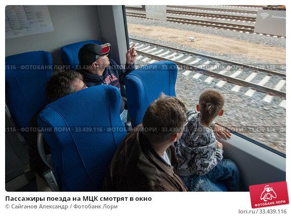 Купить «Пассажиры поезда на МЦК смотрят в окно», фото № 33439116, снято 10 сентября 2016 г. (c) Сайганов Александр / Фотобанк Лори