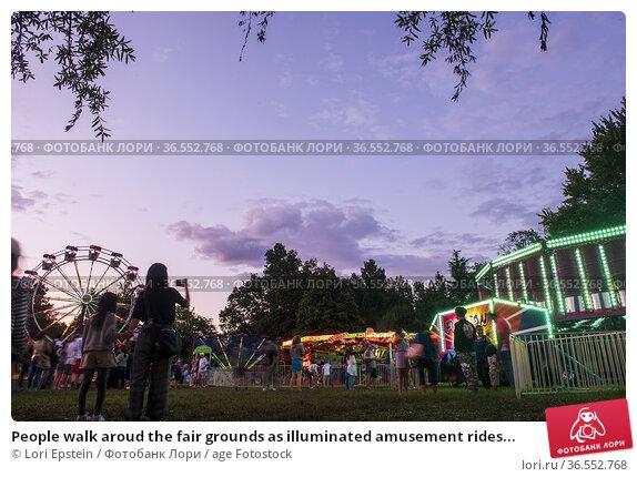 People walk aroud the fair grounds as illuminated amusement rides... Стоковое фото, фотограф Lori Epstein / age Fotostock / Фотобанк Лори