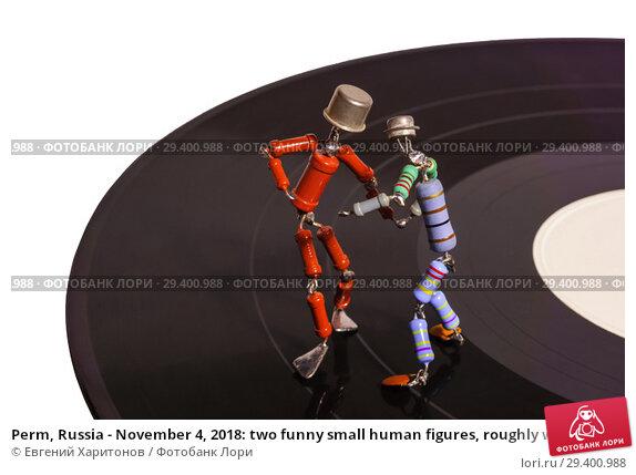 Купить «Perm, Russia - November 4, 2018: two funny small human figures, roughly welded together from resistors and transistors, dance on a vinyl record on a loght background», фото № 29400988, снято 4 ноября 2018 г. (c) Евгений Харитонов / Фотобанк Лори