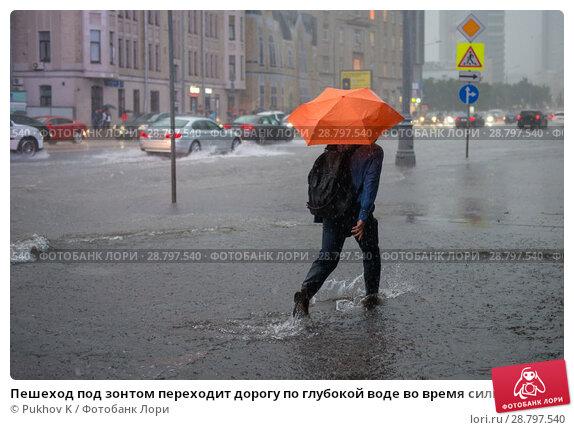 Пешеход под зонтом переходит дорогу по глубокой воде во время сильного ливня. Новый Арбат, Москва (2018 год). Редакционное фото, фотограф Pukhov K / Фотобанк Лори