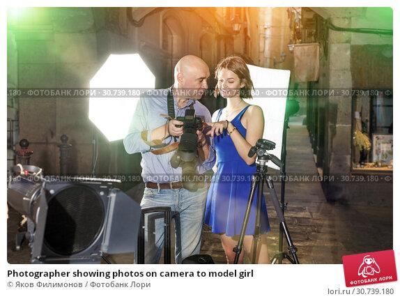 Купить «Photographer showing photos on camera to model girl», фото № 30739180, снято 5 октября 2018 г. (c) Яков Филимонов / Фотобанк Лори