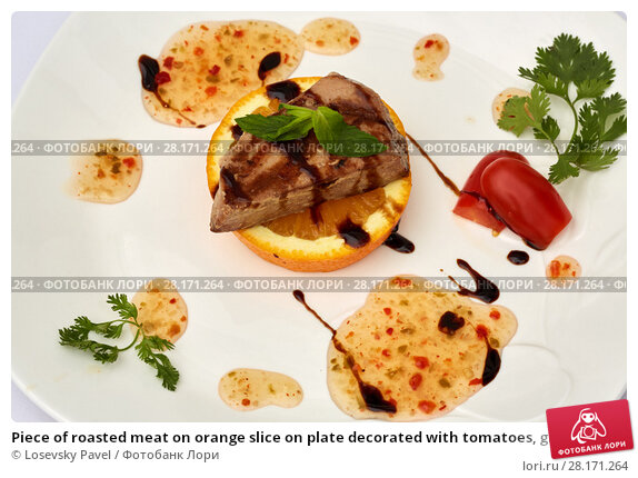 Купить «Piece of roasted meat on orange slice on plate decorated with tomatoes, greens and sauce», фото № 28171264, снято 7 июля 2016 г. (c) Losevsky Pavel / Фотобанк Лори