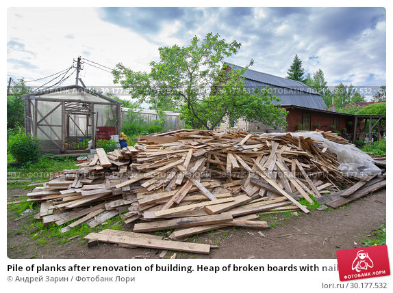 Купить «Pile of planks after renovation of building. Heap of broken boards with nails. Old boards. Repair of the building. Construction garbage», фото № 30177532, снято 17 июня 2018 г. (c) Андрей Зарин / Фотобанк Лори