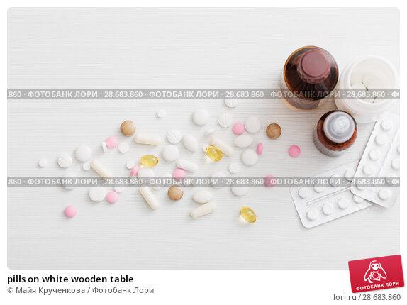 Купить «pills on white wooden table», фото № 28683860, снято 3 июля 2018 г. (c) Майя Крученкова / Фотобанк Лори