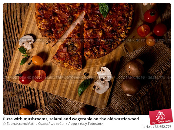 Pizza with mushrooms, salami and wegetable on the old wustic wood... Стоковое фото, фотограф Zoonar.com/Mathe Csaba / easy Fotostock / Фотобанк Лори