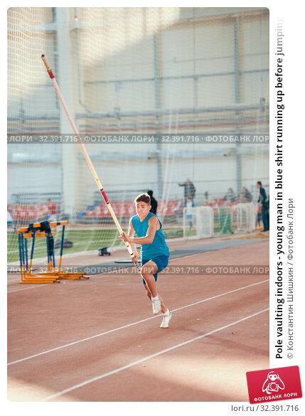 Купить «Pole vaulting indoors - young man in blue shirt running up before jumping with a pole», фото № 32391716, снято 1 ноября 2019 г. (c) Константин Шишкин / Фотобанк Лори