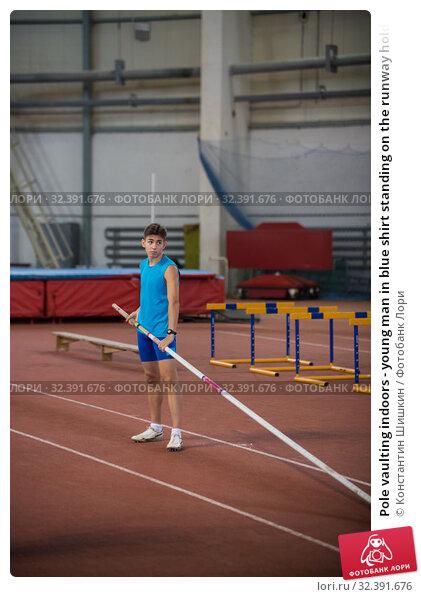 Купить «Pole vaulting indoors - young man in blue shirt standing on the runway holding a pole», фото № 32391676, снято 1 ноября 2019 г. (c) Константин Шишкин / Фотобанк Лори