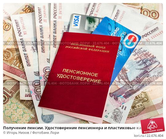 Получение пенсии. Удостоверение пенсионера и пластиковые карты лежат на российских деньгах, эксклюзивное фото № 22676404, снято 18 апреля 2016 г. (c) Игорь Низов / Фотобанк Лори