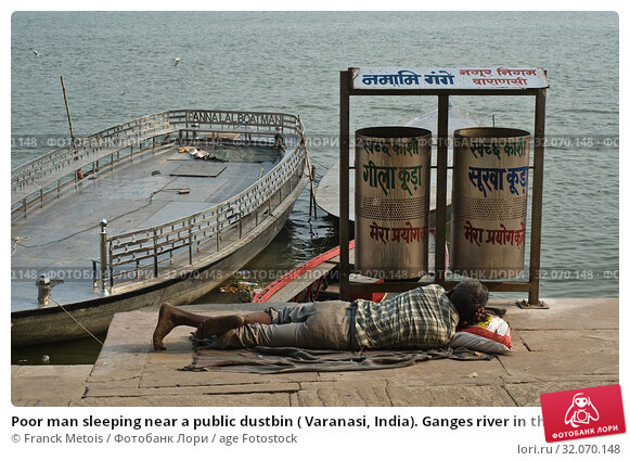 Poor man sleeping near a public dustbin ( Varanasi, India). Ganges river in the background. Стоковое фото, фотограф Franck Metois / age Fotostock / Фотобанк Лори