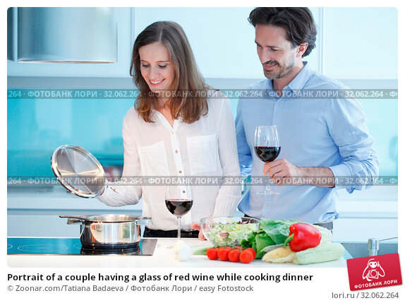 Portrait of a couple having a glass of red wine while cooking dinner. Стоковое фото, фотограф Zoonar.com/Tatiana Badaeva / easy Fotostock / Фотобанк Лори
