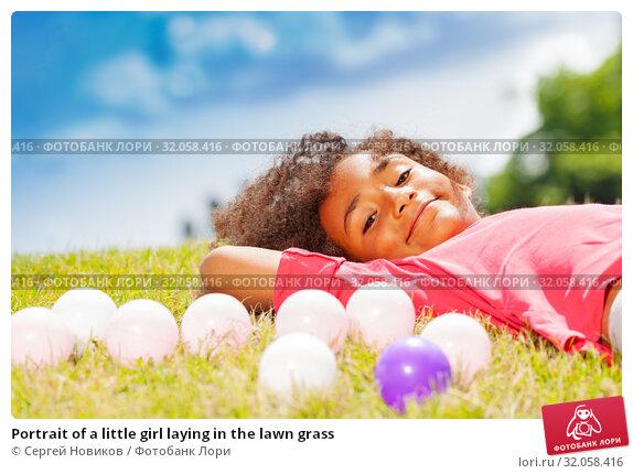 Portrait of a little girl laying in the lawn grass. Стоковое фото, фотограф Сергей Новиков / Фотобанк Лори