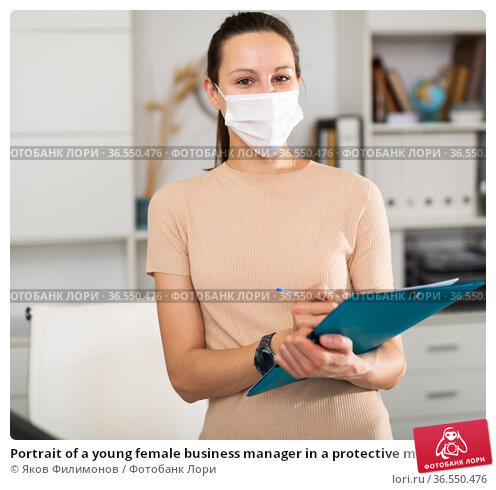 Portrait of a young female business manager in a protective mask who stands in the office and writes down important notes for work. Стоковое фото, фотограф Яков Филимонов / Фотобанк Лори