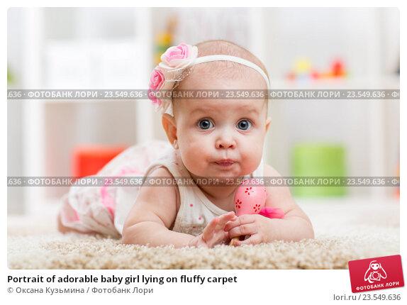 Купить «Portrait of adorable baby girl lying on fluffy carpet», фото № 23549636, снято 7 октября 2015 г. (c) Оксана Кузьмина / Фотобанк Лори