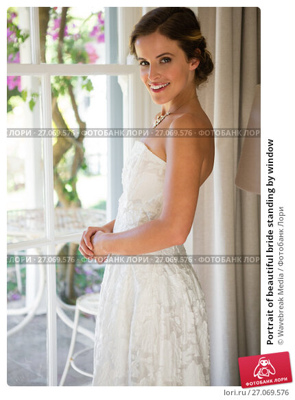 Portrait of beautiful bride standing by window, фото № 27069576, снято 2 мая 2017 г. (c) Wavebreak Media / Фотобанк Лори
