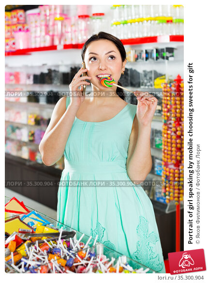 Portrait of girl speaking by mobile choosing sweets for gift. Стоковое фото, фотограф Яков Филимонов / Фотобанк Лори