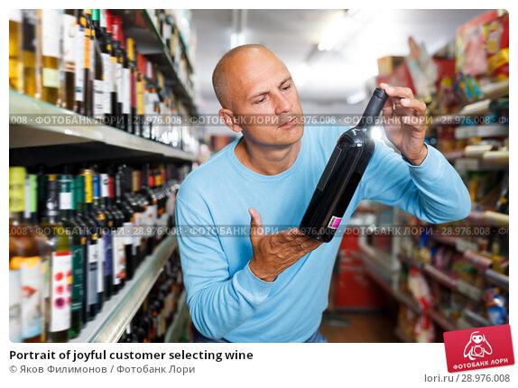 Купить «Portrait of joyful customer selecting wine», фото № 28976008, снято 4 июля 2018 г. (c) Яков Филимонов / Фотобанк Лори
