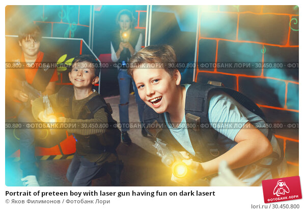 Portrait of preteen boy with laser gun having fun on dark lasert. Стоковое фото, фотограф Яков Филимонов / Фотобанк Лори
