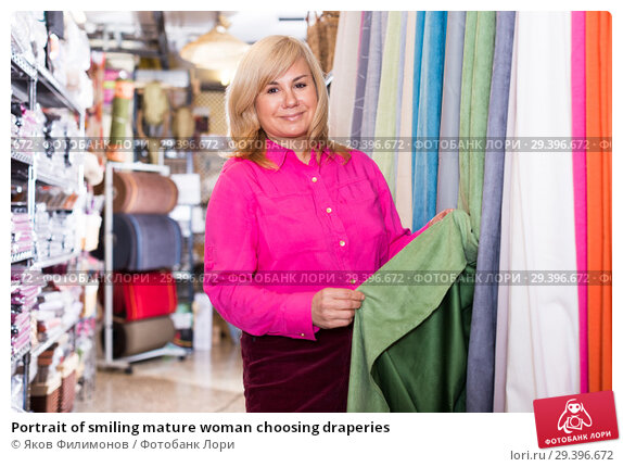 Купить «Portrait of smiling mature woman choosing draperies», фото № 29396672, снято 17 января 2018 г. (c) Яков Филимонов / Фотобанк Лори