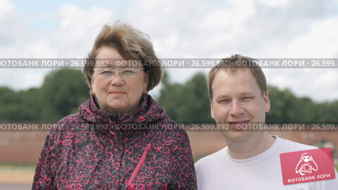 Купить «Portrait of two smiling adult woman and young man», видеоролик № 26599892, снято 30 июня 2017 г. (c) worker / Фотобанк Лори