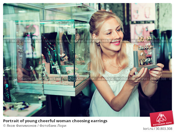 Купить «Portrait of young cheerful woman choosing earrings», фото № 30803308, снято 17 июня 2019 г. (c) Яков Филимонов / Фотобанк Лори