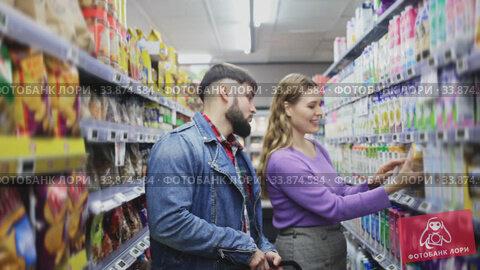 Portrait of young loving couple walking among shelves with groceries in supermarket. Стоковое видео, видеограф Яков Филимонов / Фотобанк Лори