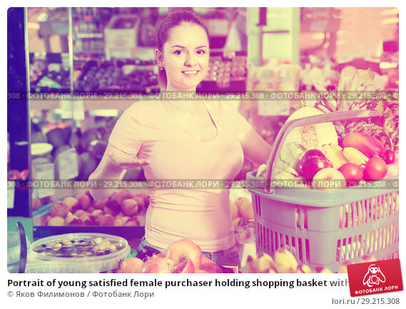 Купить «Portrait of young satisfied female purchaser holding shopping basket with fruits and vegetables», фото № 29215308, снято 14 октября 2017 г. (c) Яков Филимонов / Фотобанк Лори