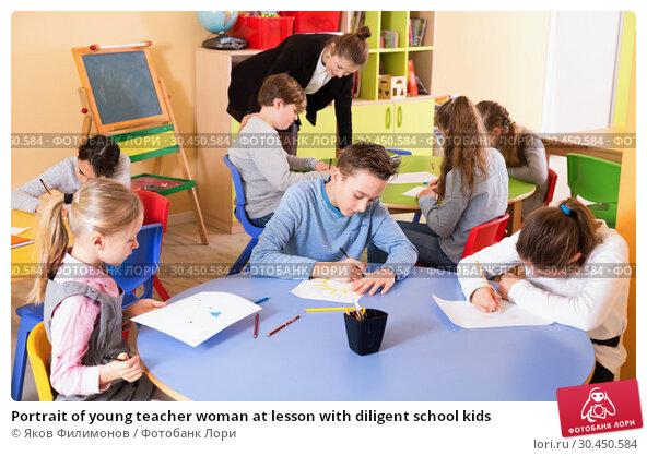 Portrait of young teacher woman at lesson with diligent school kids. Стоковое фото, фотограф Яков Филимонов / Фотобанк Лори