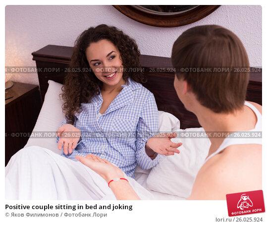 Positive couple sitting in bed and joking, фото № 26025924, снято 29 апреля 2017 г. (c) Яков Филимонов / Фотобанк Лори