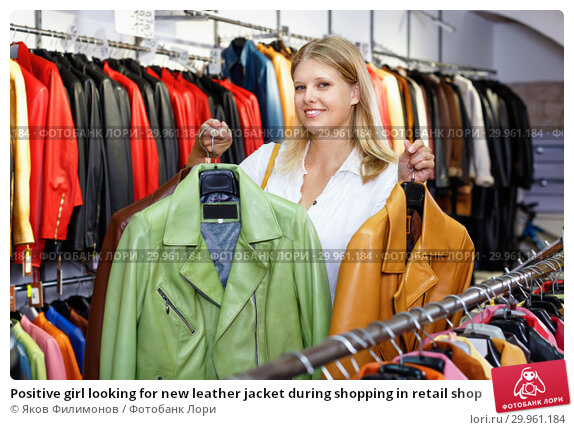 Купить «Positive girl looking for new leather jacket during shopping in retail shop», фото № 29961184, снято 5 сентября 2018 г. (c) Яков Филимонов / Фотобанк Лори
